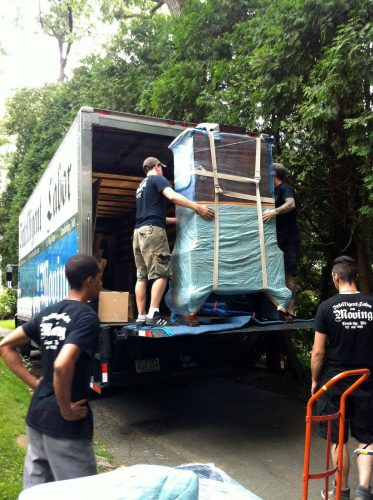 An armoire on a lift gate wrapped and strapped for moving.