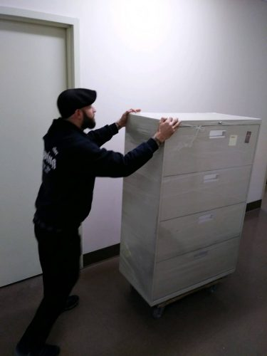 vinnie pushing a file cabinet on an office move